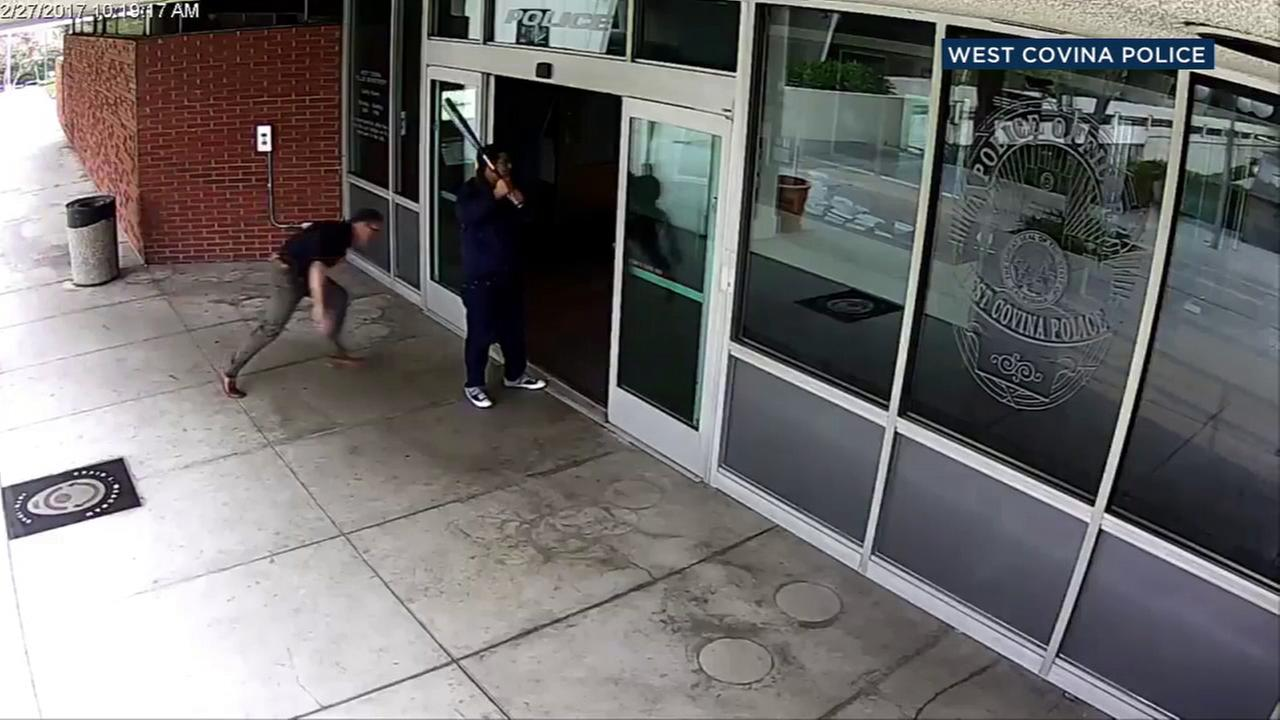 A surveillance image shows an officer lunging toward a man wielding a bat in front of the West Covina Police Department on Monday, Feb. 27, 2017.