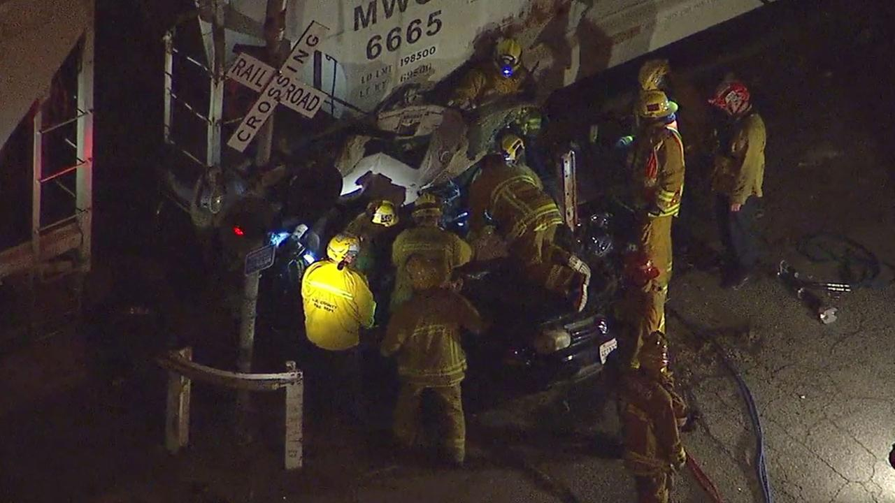 Firefighters worked to pull a woman out of a mangled car after it crashed with a freight train in Commerce on Friday, March 10, 2017.