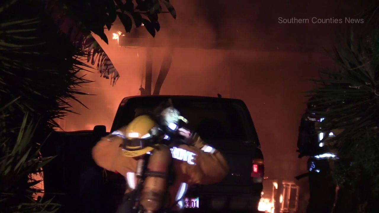 Firefighters are seen outside a burning home in Santa Ana on Saturday, March 11, 2017.
