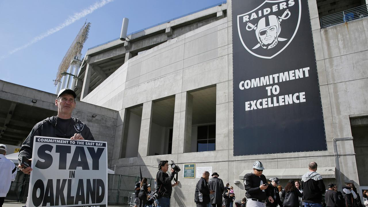 John P. Kelleher holds up a sign outside the Oakland Coliseum before the start of a rally to keep the Oakland Raiders from moving Saturday, March 25, 2017, in Oakland.