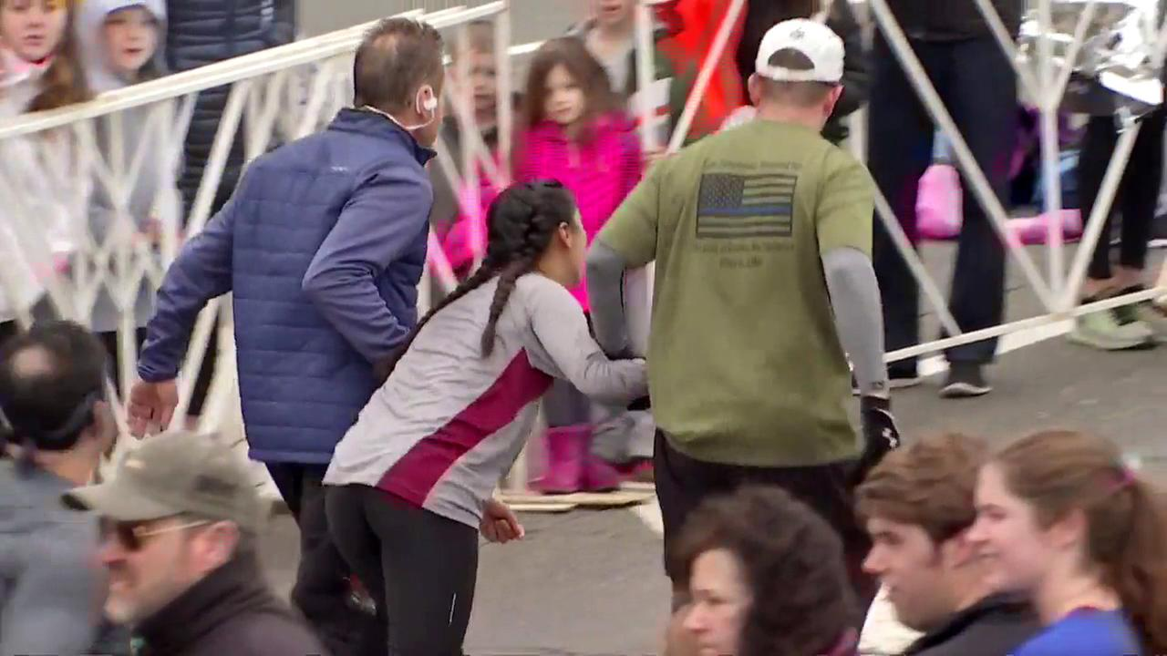 Two fellow runners helped a fatigued woman approach the end of a half-marathon in Philadelphia on Sunday, March 26, 2017, before a third man carried her to the finish line.