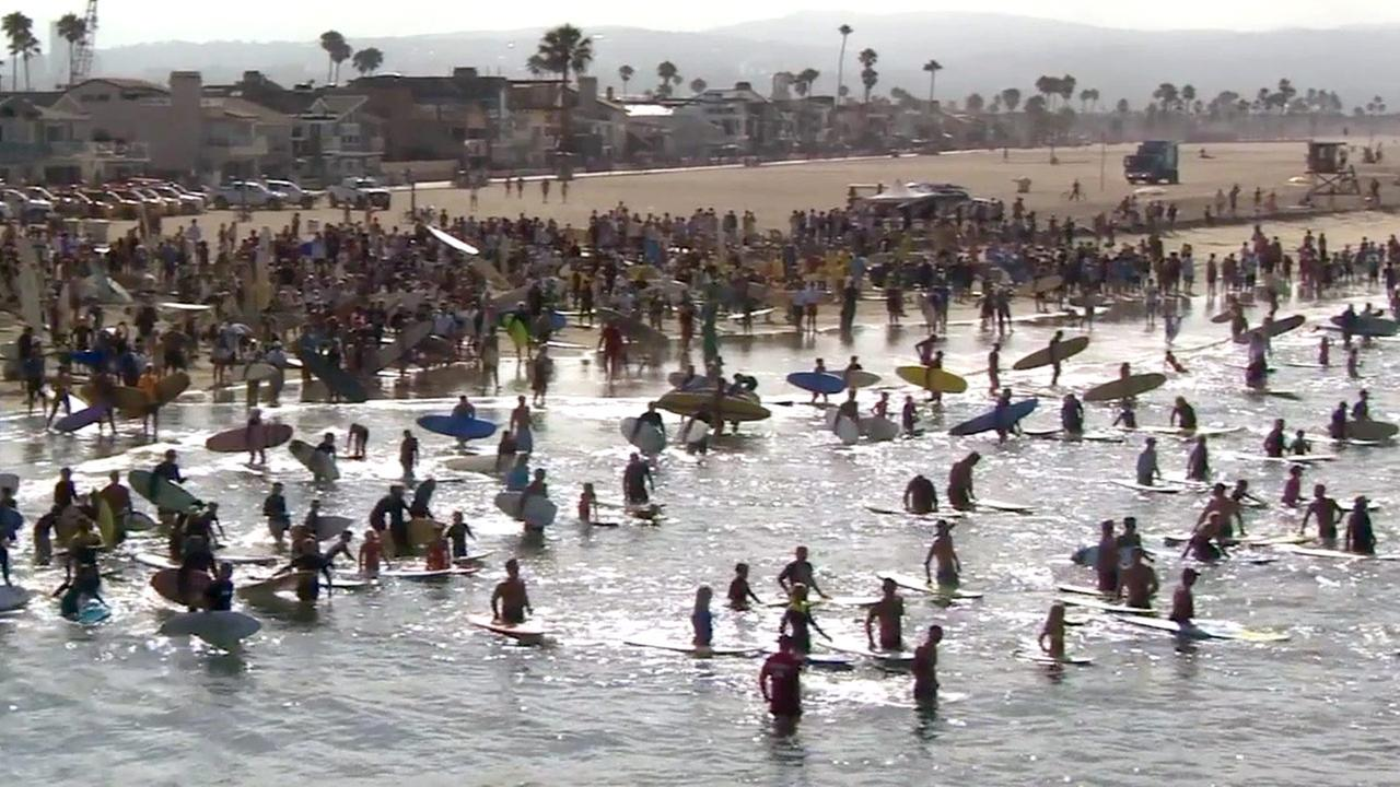 Hundreds of people paddled out on their surfboards in Newport Beach to honor the lifeguard who drowned trying to save a distressed swimmer on Sunday, July 13, 2014,
