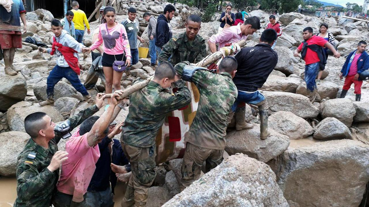 In this handout photo released by the Colombian National Army, soldiers and residents work together in rescue efforts in Mocoa, Colombia, Saturday, April 1, 2017.