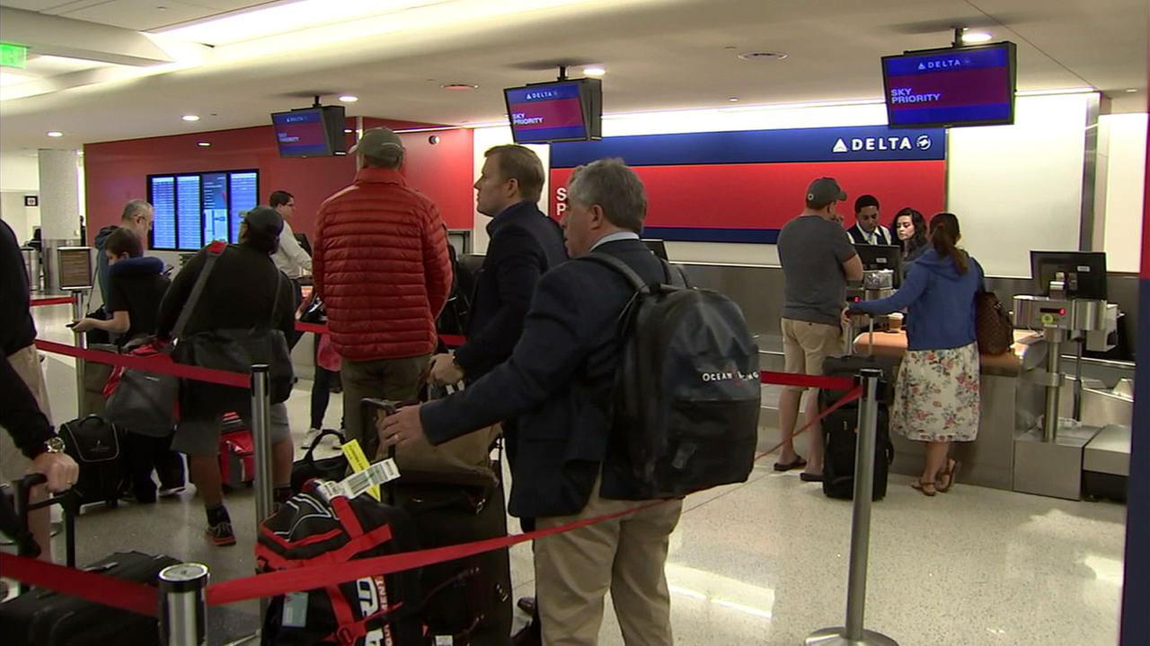 Delta Air Lines passengers wait in line at Los Angeles International Airport on Sunday, April 9, 2017.