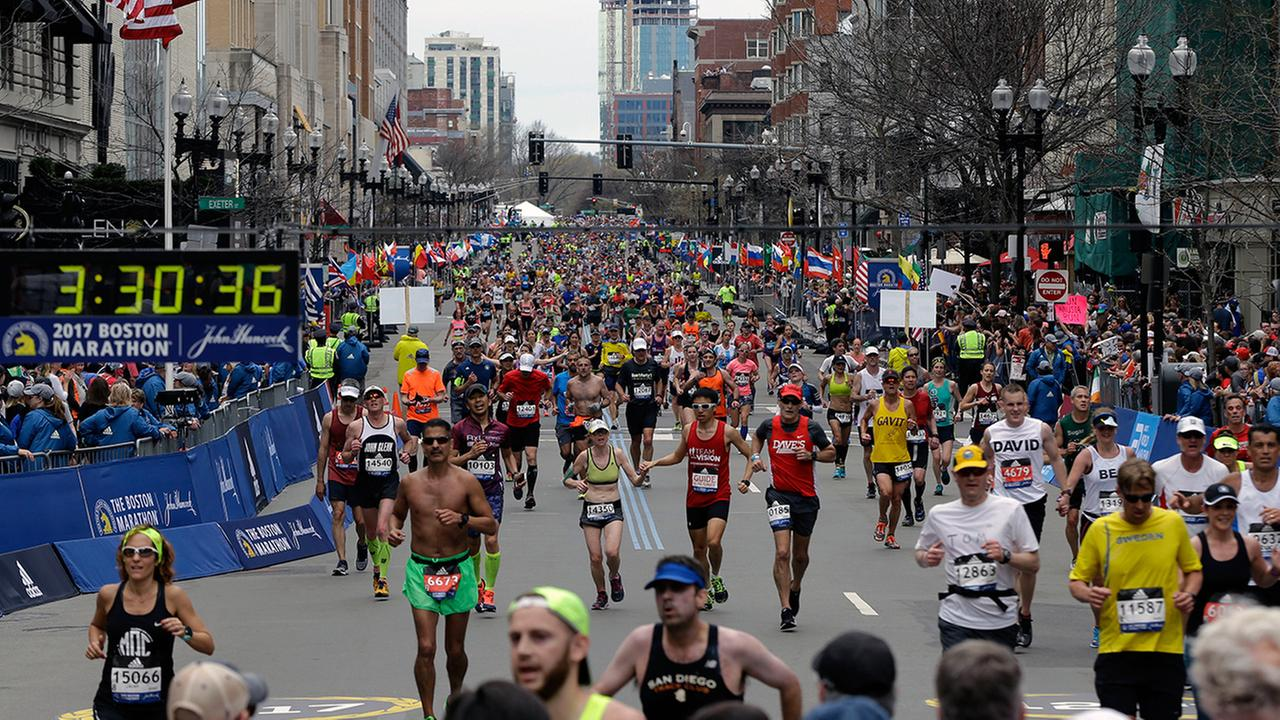 In this Monday, April 17, 2017, file photo, runners head to the finish line in the 121st Boston Marathon in Boston.