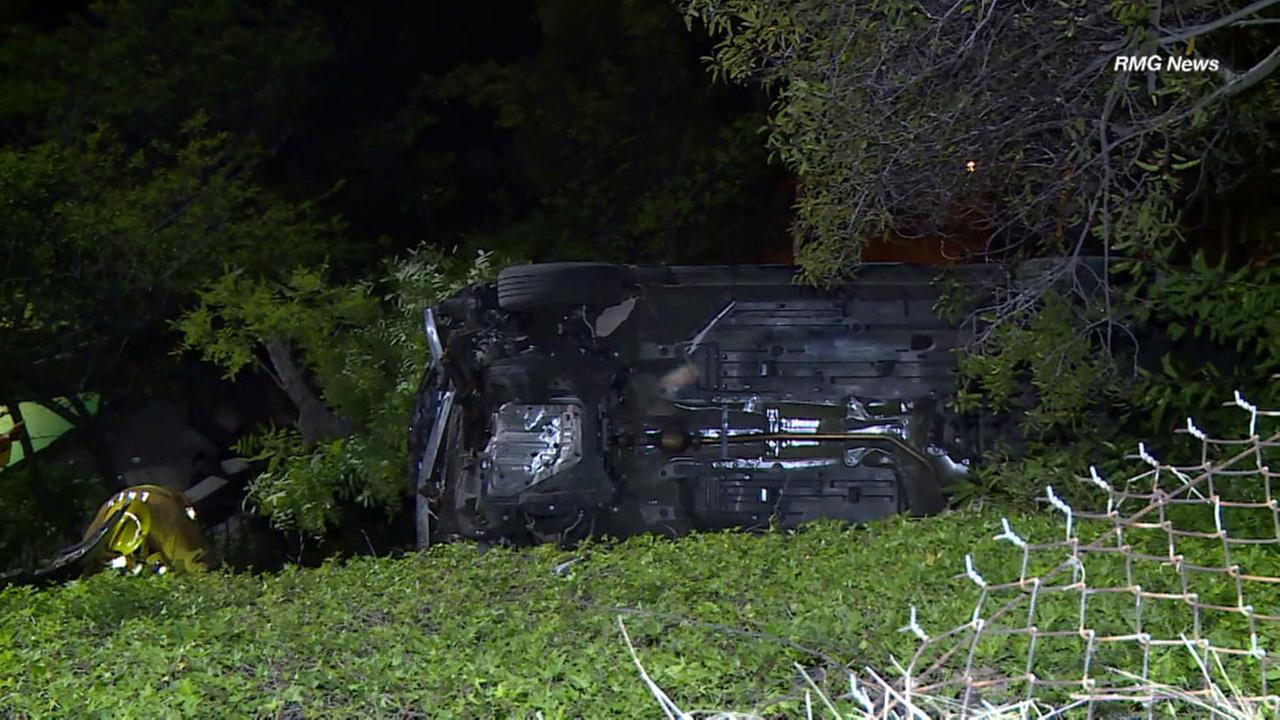 A car is on its side in the Hollywood Hills after it plunged down a cliff on Friday, April 21, 2017.