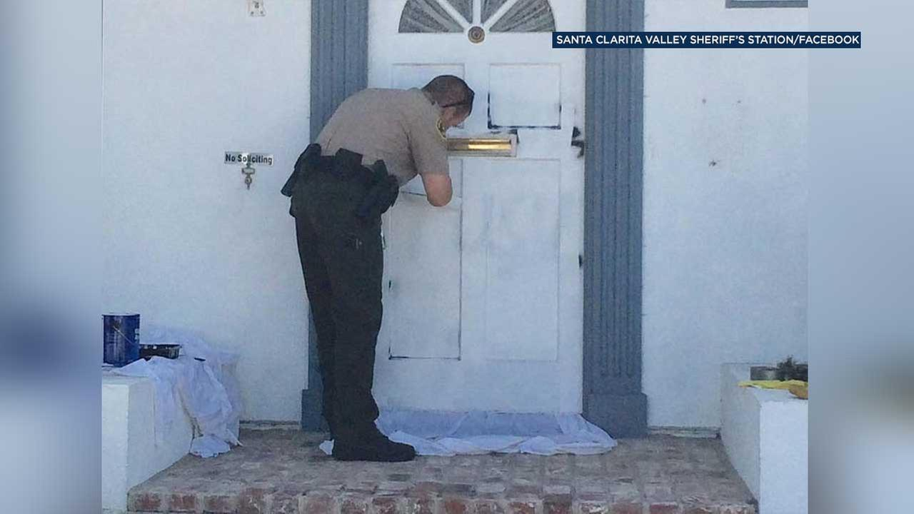 Deputy Scott Peterson is seen painting over graffiti on a door at the home of a Saugus widow in this photo posted to the Santa Clarita Valley Sheriffs Stations Facebook page.