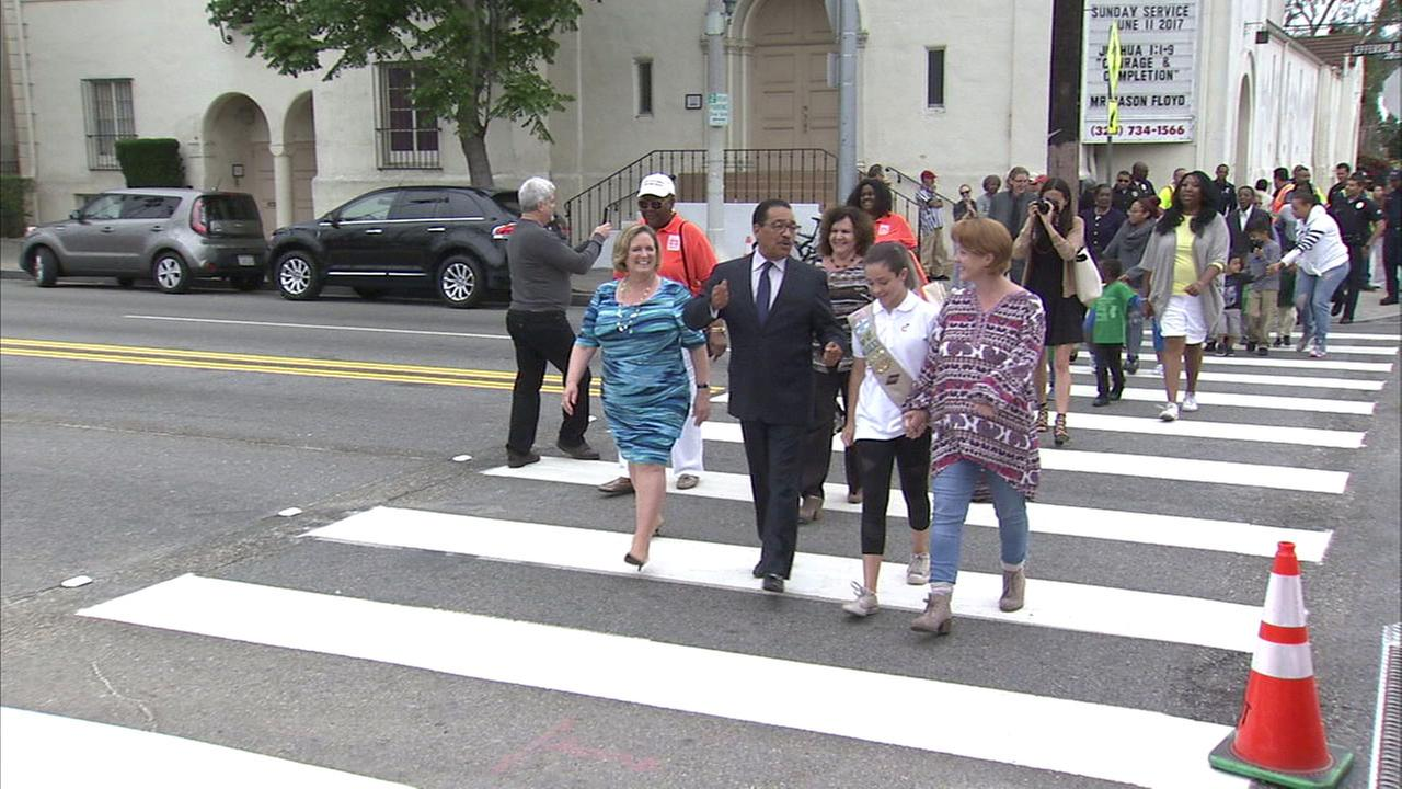 Girl Scout Gwendolyn Rudd (2nd from right) walks with City Council President Herb Wesson on the Jefferson Park crosswalk that now has a lighted signal thanks to her work.