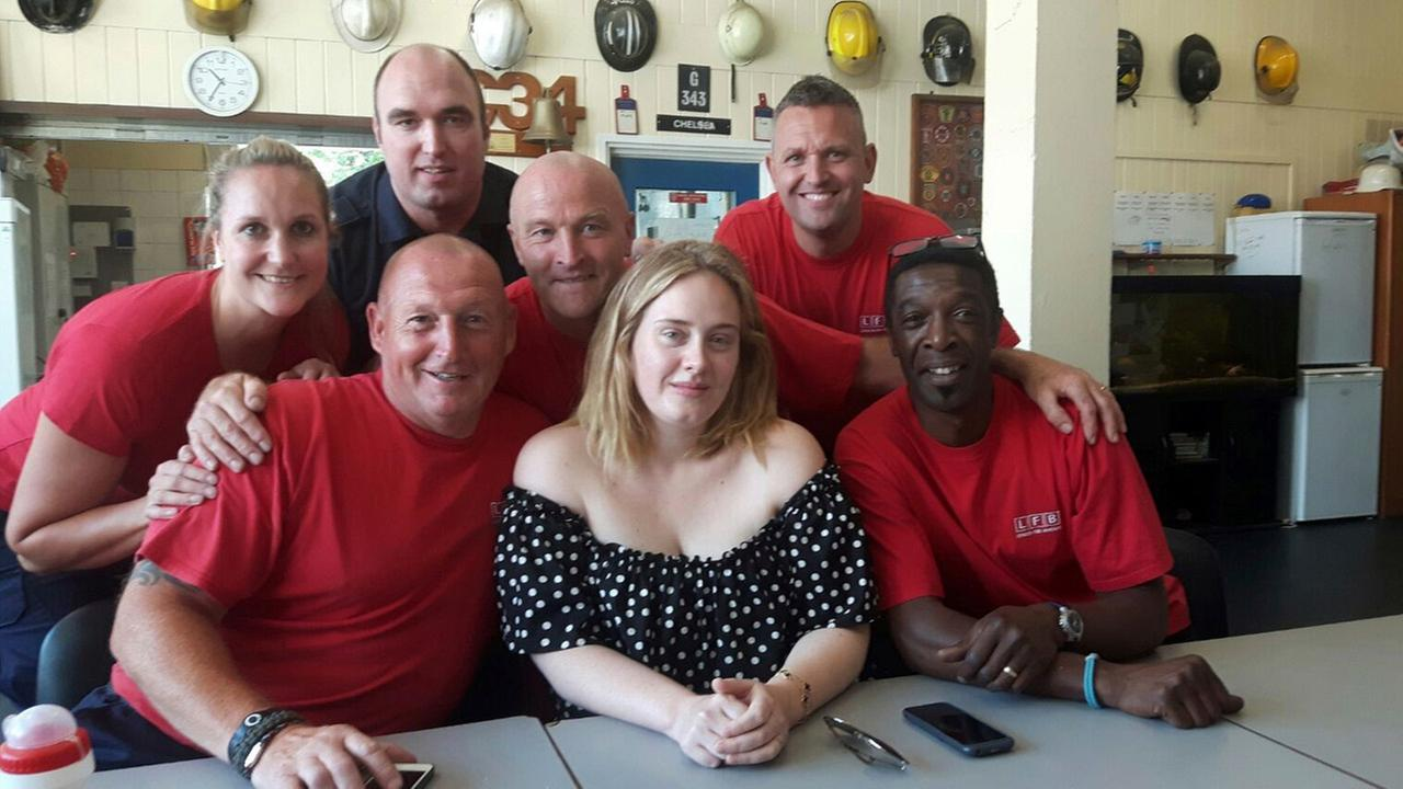 This is a London Fire Brigade handout photo taken on June 19, 2017 of pop-star Adele as she meets firefighters at Chelsea Fire Station for following the Grenfell Tower blaze.