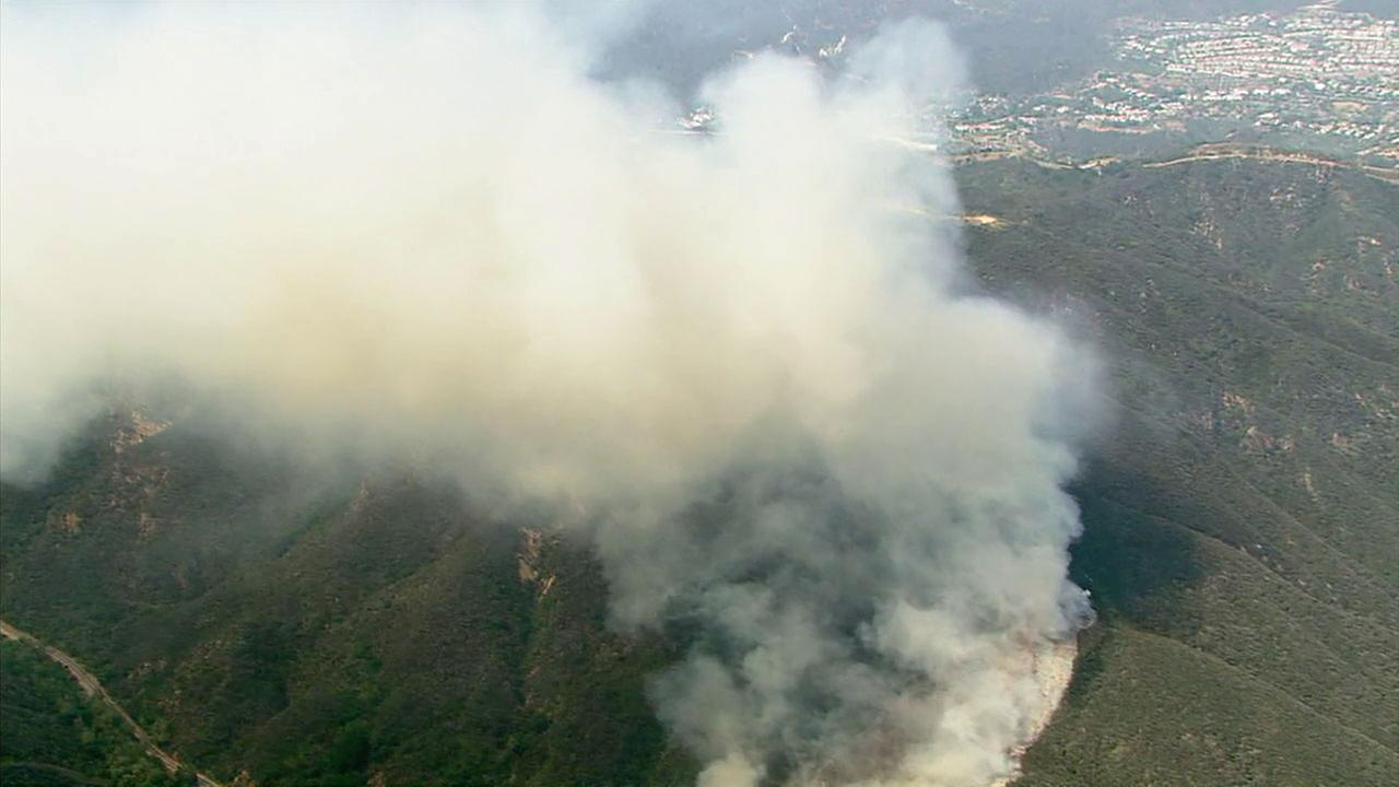 A brush fire had burned through 20-25 acres on a Malibu hillside a ridge side away from the Getty Villa.