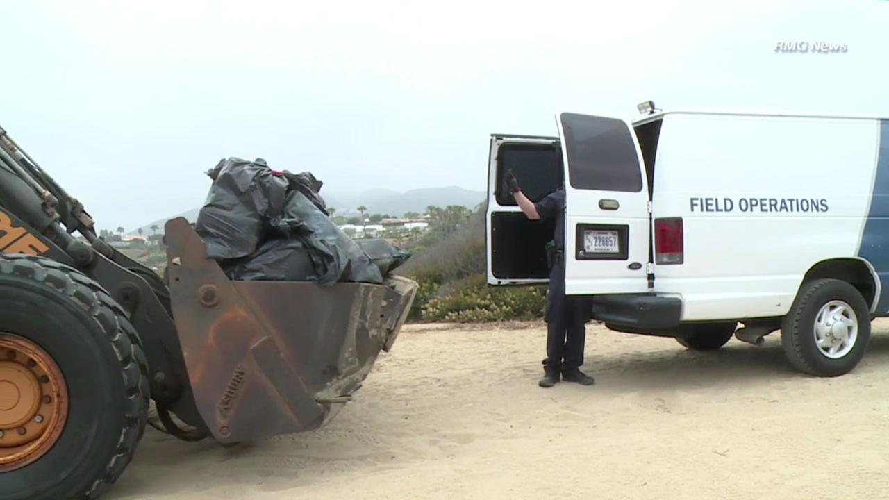 Authorities hauled 800 pounds of marijuana in bags found inside a boat left on a Malibu beach over to a truck to be investigated.