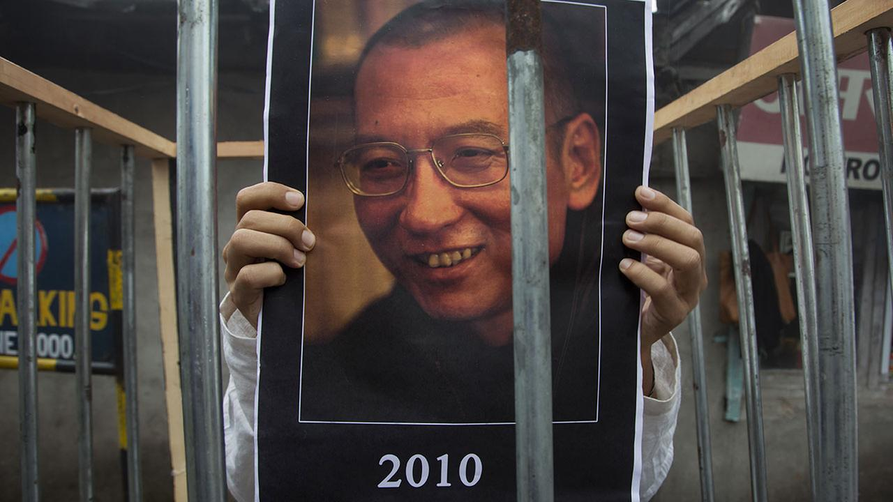 An exile Tibetan holds a portrait of the Chinese Nobel laureate Liu Xiaobo behind bars during a street protest Wednesday, July 12, 2017.
