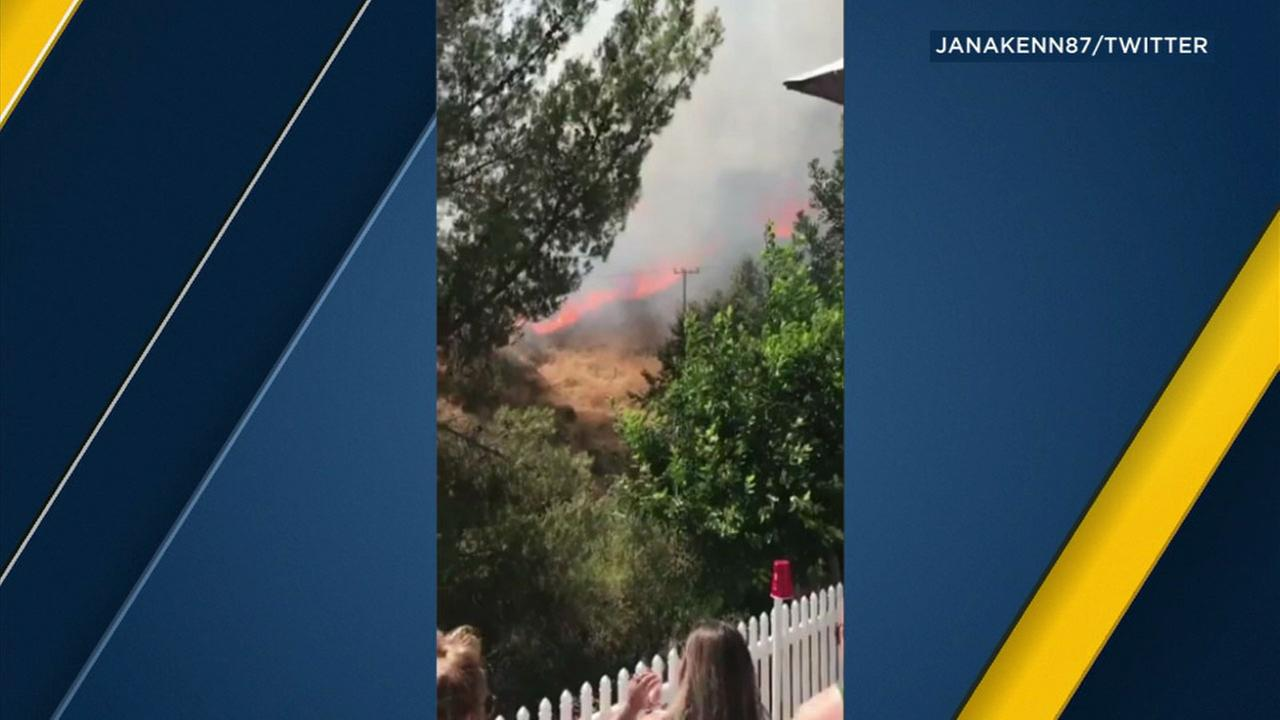A witness captured flames burning not far from a home in the hillsides of Highland on Saturday, July 22, 2017.