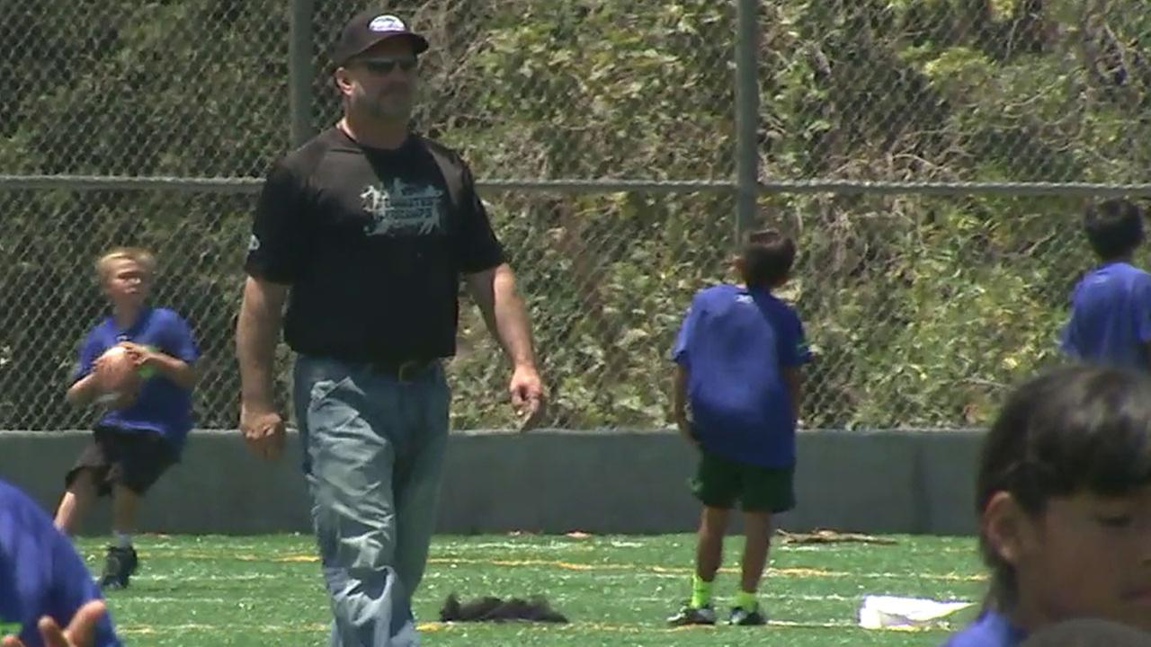 In town for a four-concert run, Garth Brooks joined Rams players to help SoCal kids with a football camp run by his nonprofit foundation.