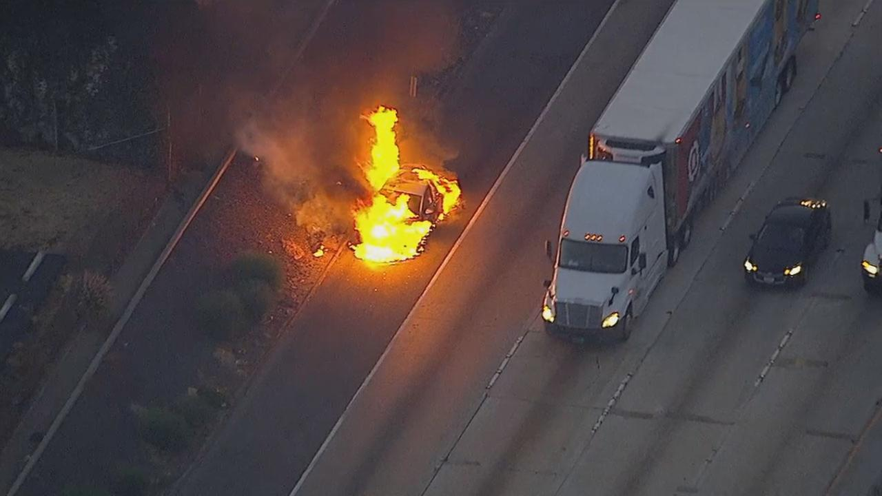A car engulfed in flames on the shoulder of the 5 Freeway in Commerce, which caused a major backup during the morning commute on Wednesday, July 26, 2017.