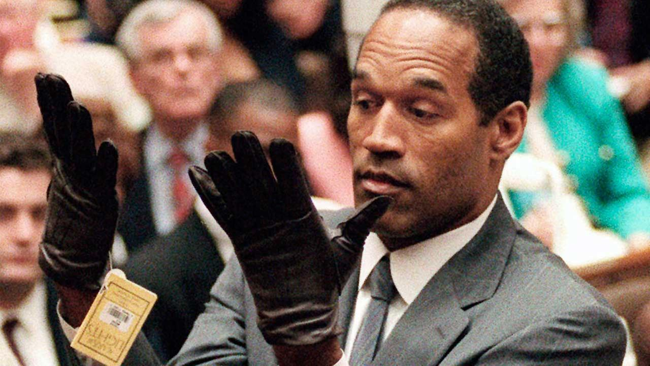 In this 1995 file photo, O.J. Simpson holds up his hands before the jury after putting on a new pair of gloves similar to the infamous bloody gloves during his double-murder trial.