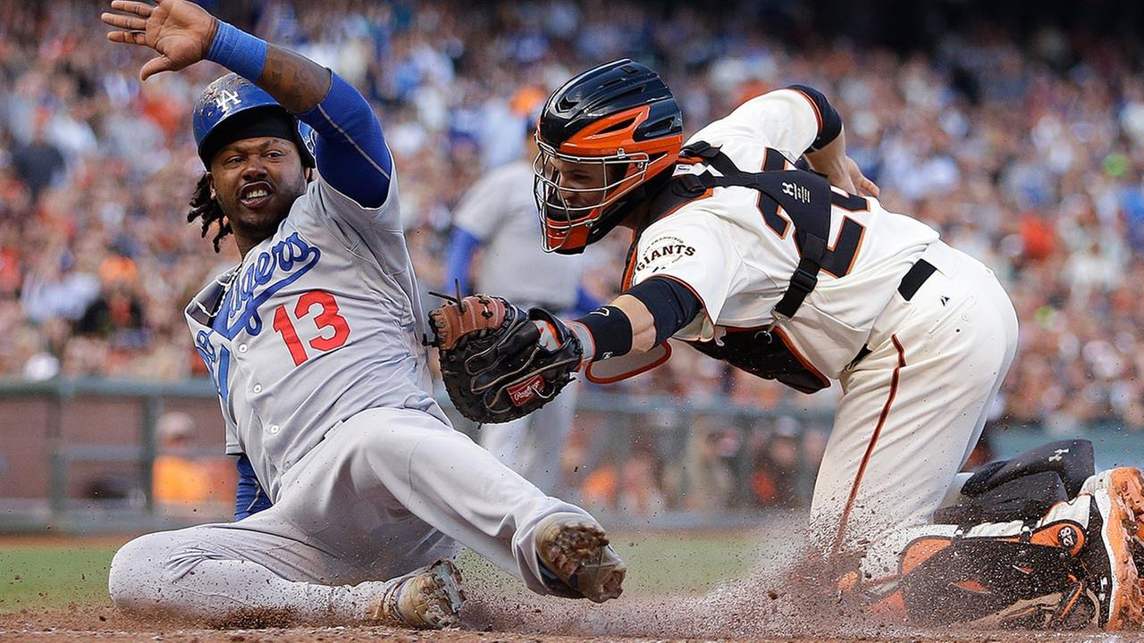 Los Angeles Dodgers Hanley Ramirez, left, scores past San Francisco Giants catcher Buster Posey in the fifth inning of a baseball game Sunday, July 27, 2014, in San Francisco.