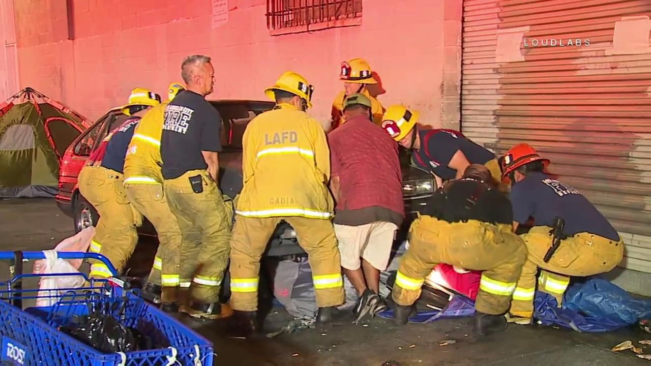 Los Angeles Fire Department firefighters lift a car off of a man after an apparent DUI crash on skid row on Saturday, Aug. 5, 2017.