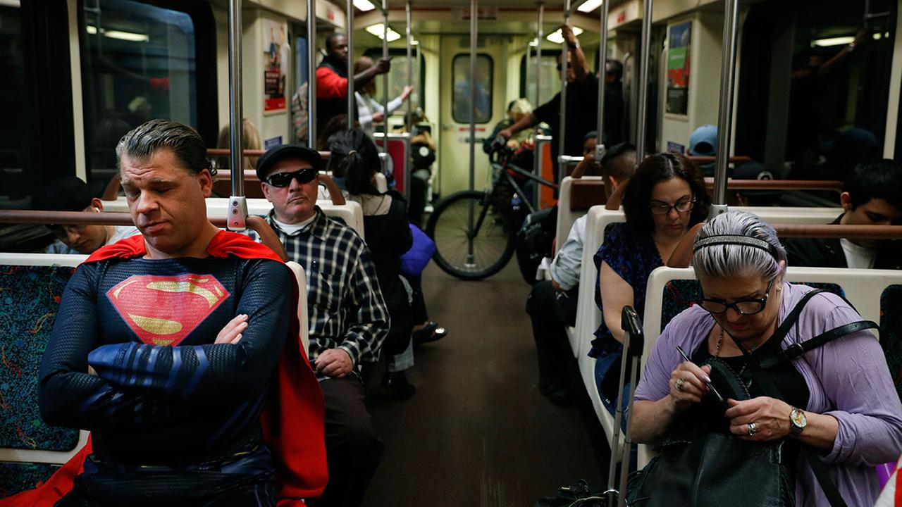 In this Tuesday, May 16, 2017 photo, superhero impersonator Justin Harrison, left, rides a Metro train wearing a Superman costume on his way to Hollywood Boulevard in Los Angeles.