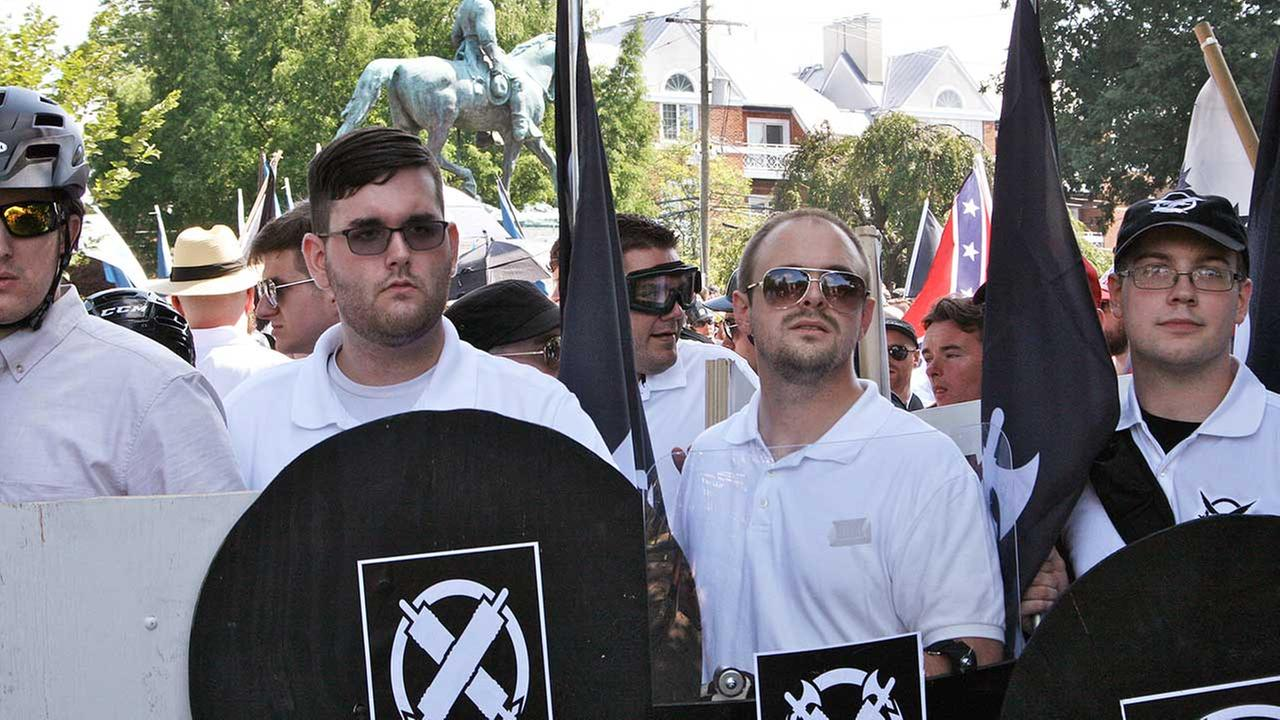 In this Saturday, Aug. 12, 2017 photo, James Alex Fields Jr., second from left, holds a black shield in Charlottesville, Virginia, where a white supremacist rally took place.