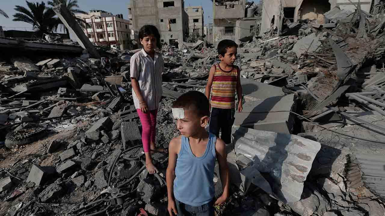 Palestinian Seraj Ismail Abdel Al, 5, lightly wounded in an overnight Israeli strike, inspects the damage to several buildings in Gaza City, Gaza Strip, Saturday, Aug. 2, 2014.