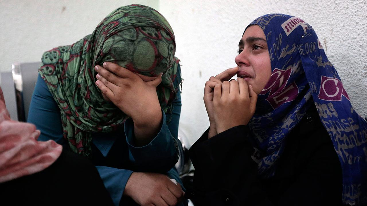 Palestinian relatives cry outside the morgue of the Kamal Adwan hospital in Beit Lahiya on Sunday, Aug. 3, 2014.