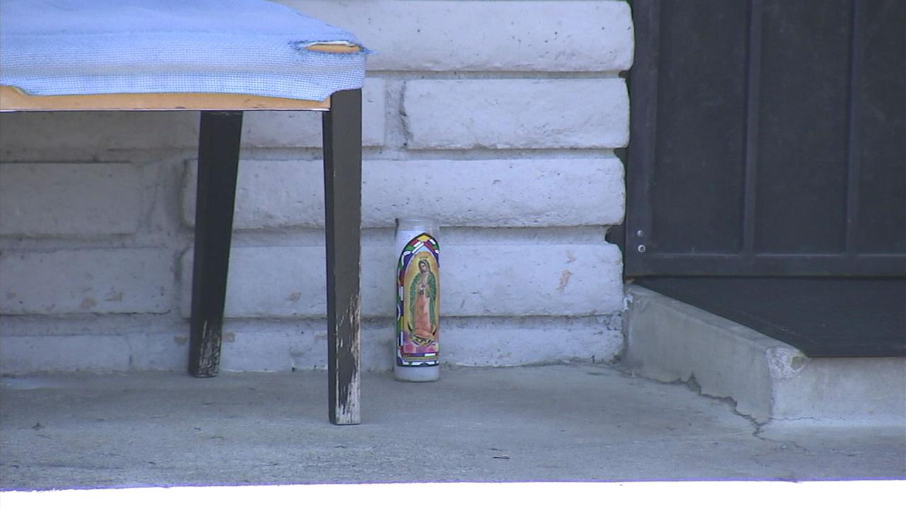 A candle is placed in front of a home where a man is suspected of killing his father in Del Rey.