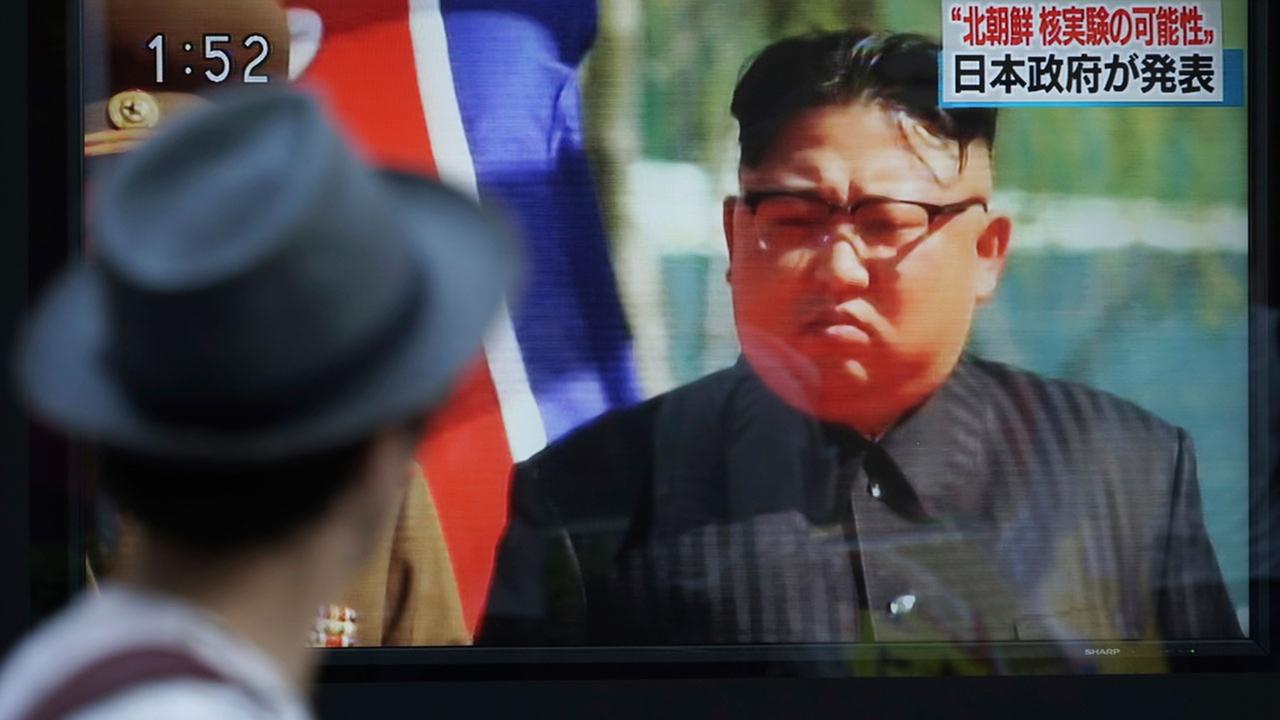 A man watches a TV news program on a public screen showing an image of North Korean leader Kim Jong Un.