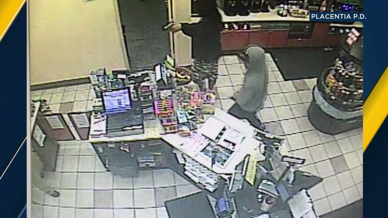 Two armed robbery suspects are shown holding up a Placentia gas station clerk and stealing money on Saturday, Sept. 16, 2017.
