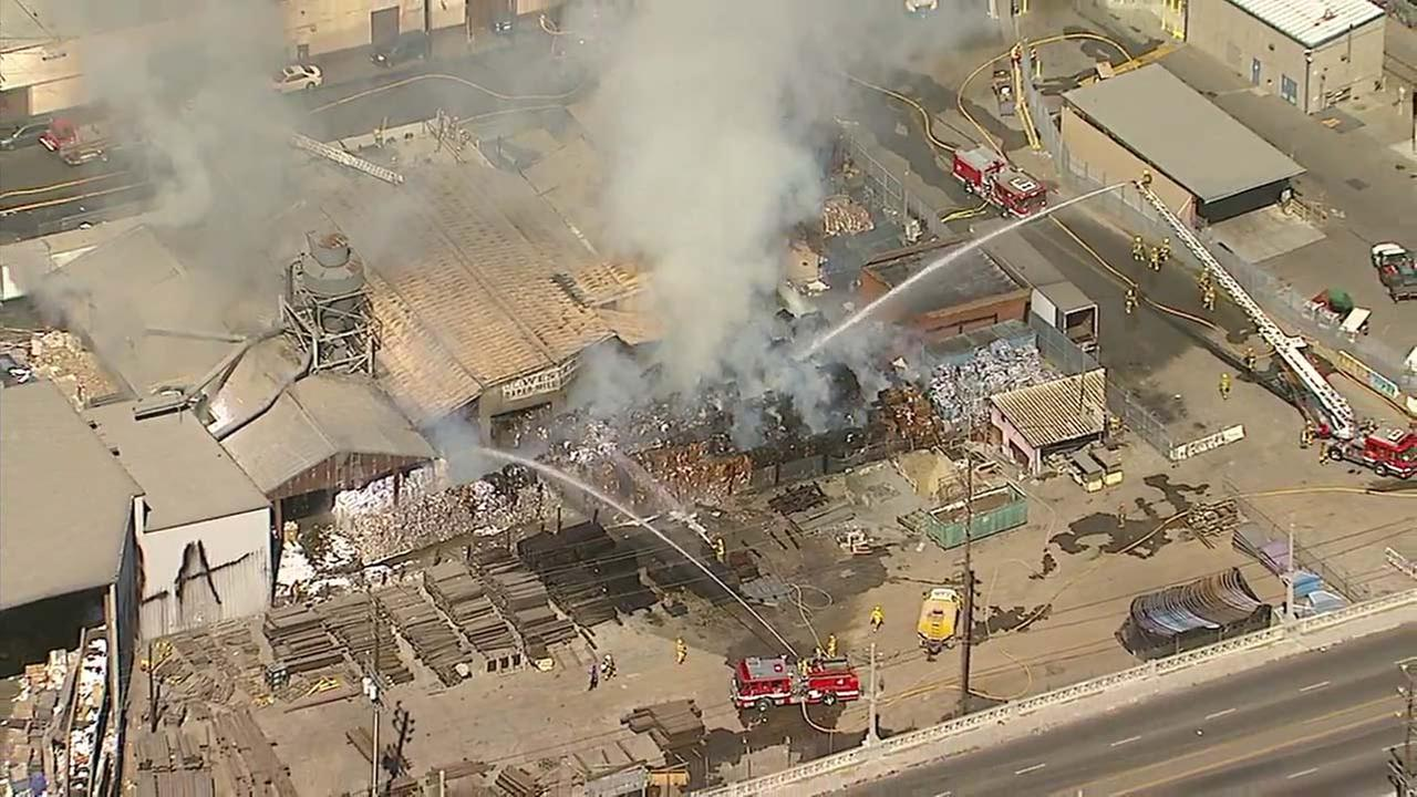 Fire crews douse a fire at a paper recycling facility near downtown Los Angeles on Thursday, Oct. 5, 2017.