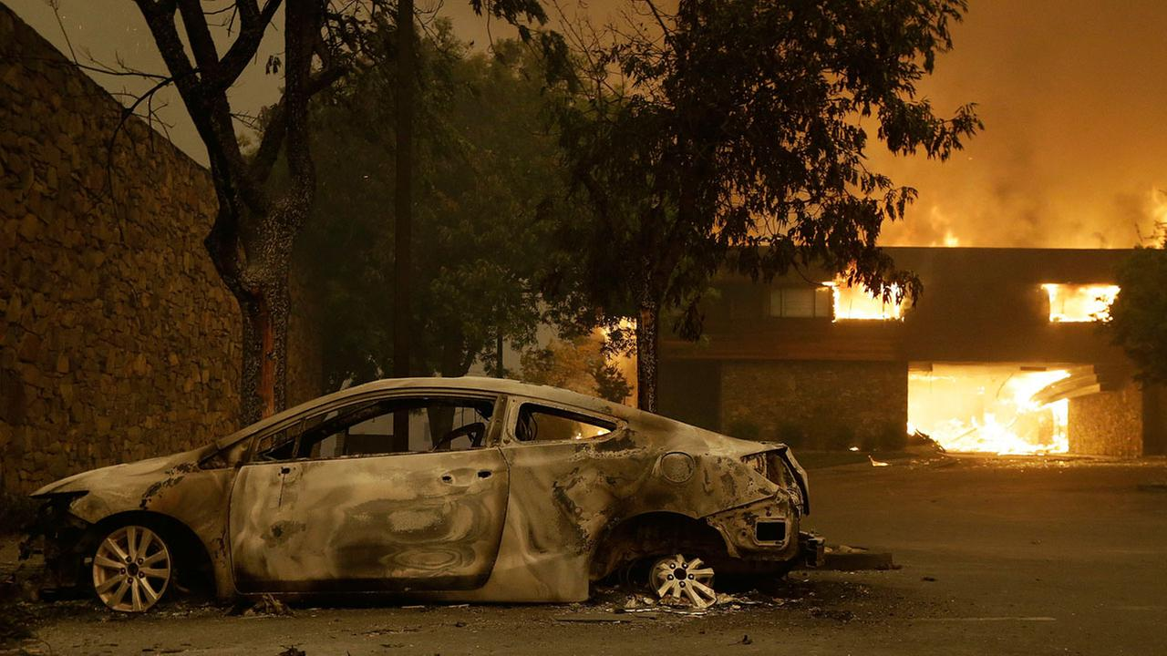 The remains of a car sits near the Fountaingrove Inn Hotel as it burns at rear in Santa Rosa, Calif., Monday, Oct. 9, 2017.
