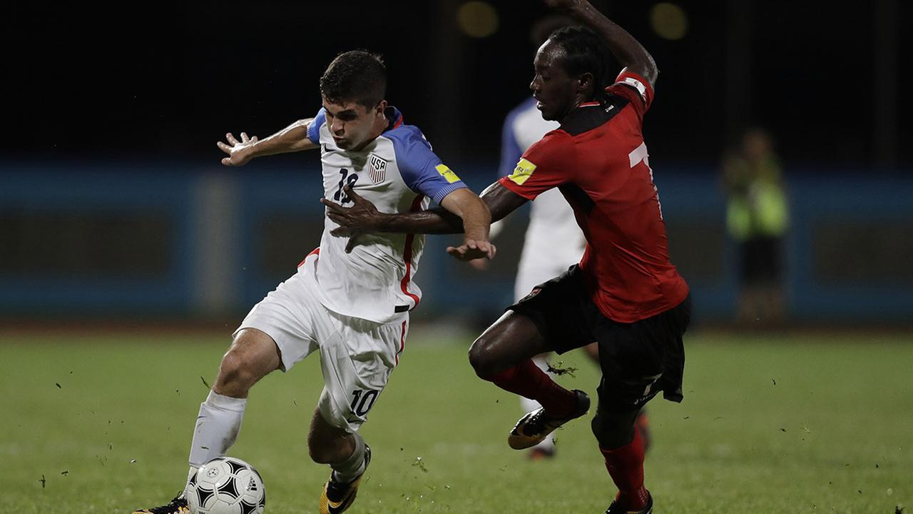 United States Christian Pulisic, left, fight for the ball with Trinidad and Tobagos Nathan Lewis during a 2018 World Cup qualifying soccer match Tuesday, Oct. 10, 2017.