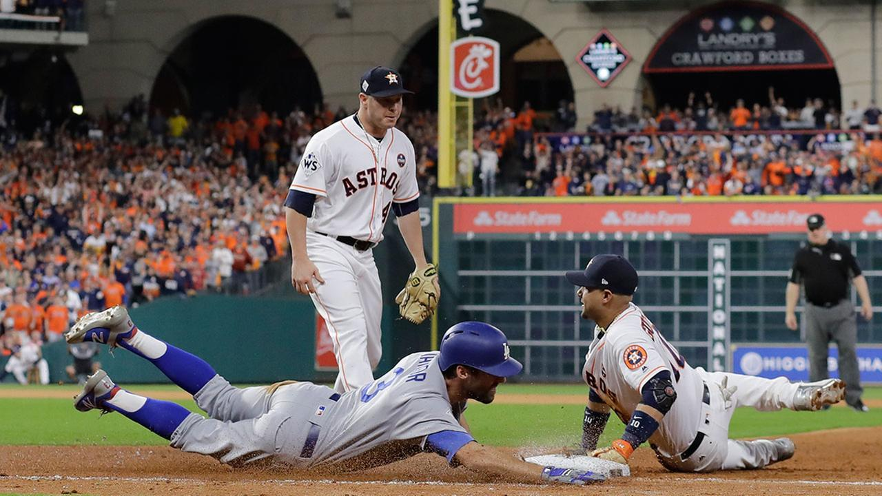 Houston Astros Yuli Gurriel dives to first to force out Los Angeles Dodgers Chris Taylor during Game 3 of the World Series Friday, Oct. 27, 2017, in Houston.