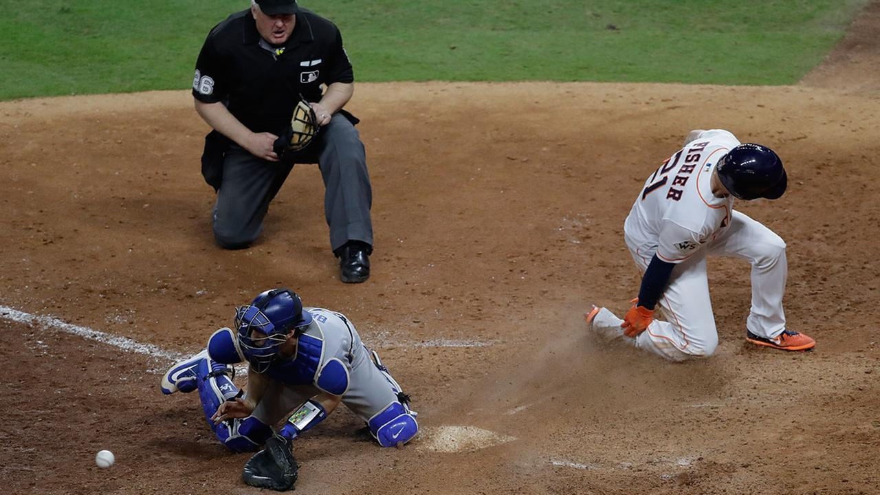 Astros Derek Fisher scores past Los Angeles Dodgers catcher Austin Barnes for the game-winning run during Game 5 of the World Series Monday, Oct. 30, 2017, in Houston.