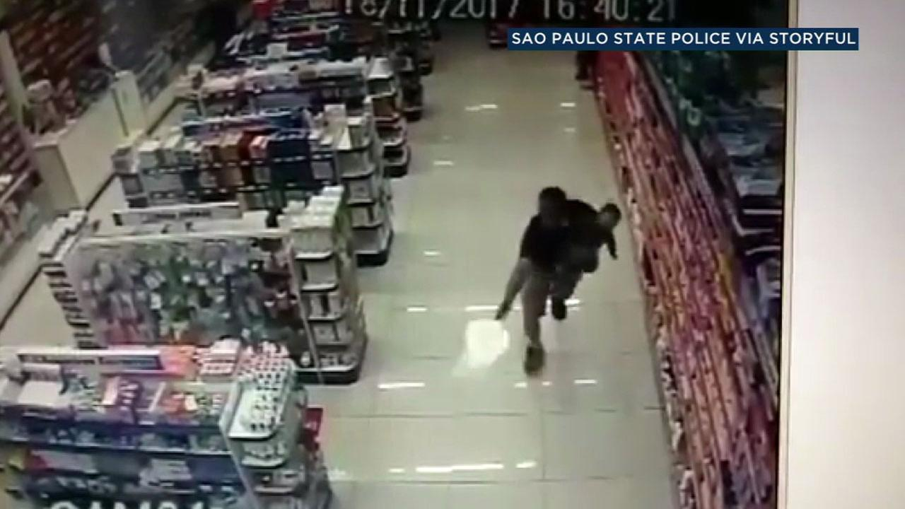 An off-duty Brazilian officer fired his gun at armed robbers while he held his child inside a pharmacy.