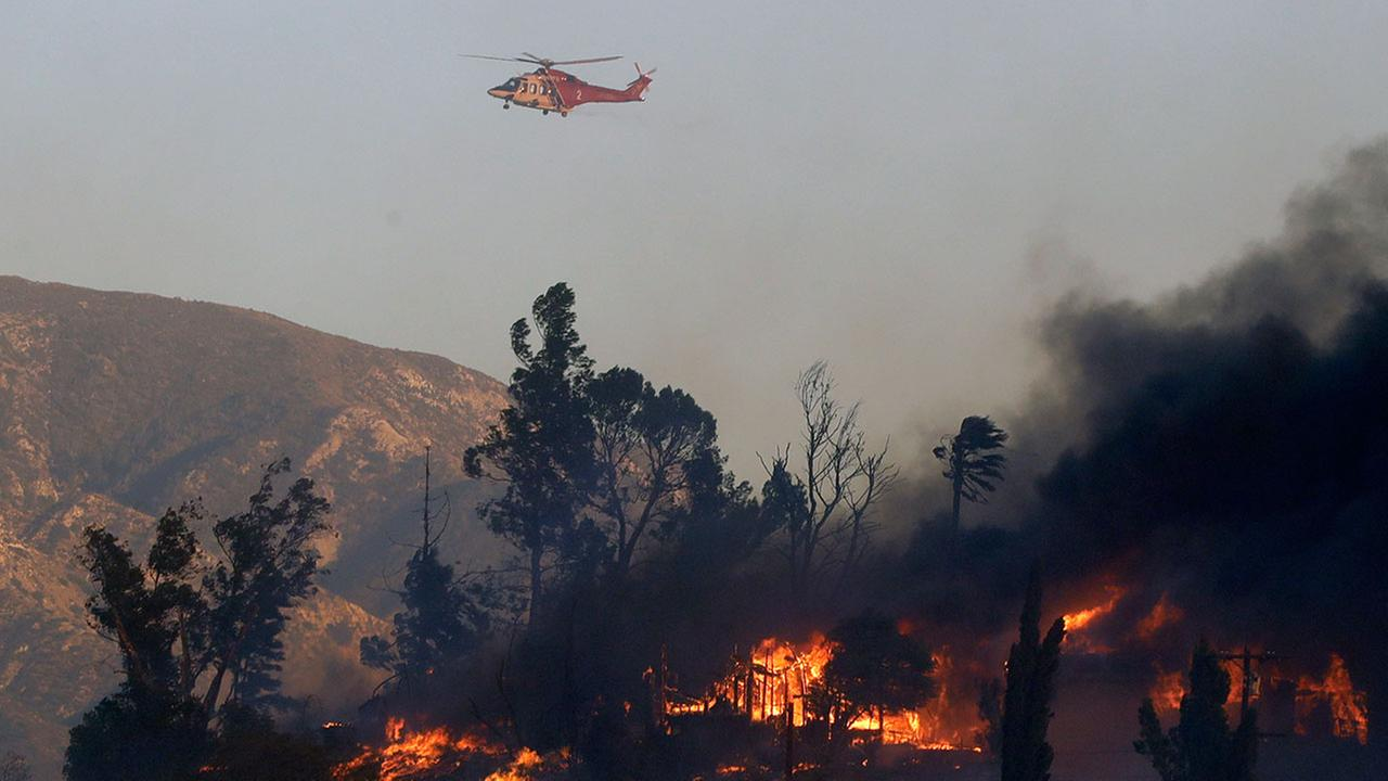 A water dropping helicopter flies over a hot spot on the Creek Fire in the Lake View Terrace area of Los Angeles, Tuesday, Dec. 5, 2017.