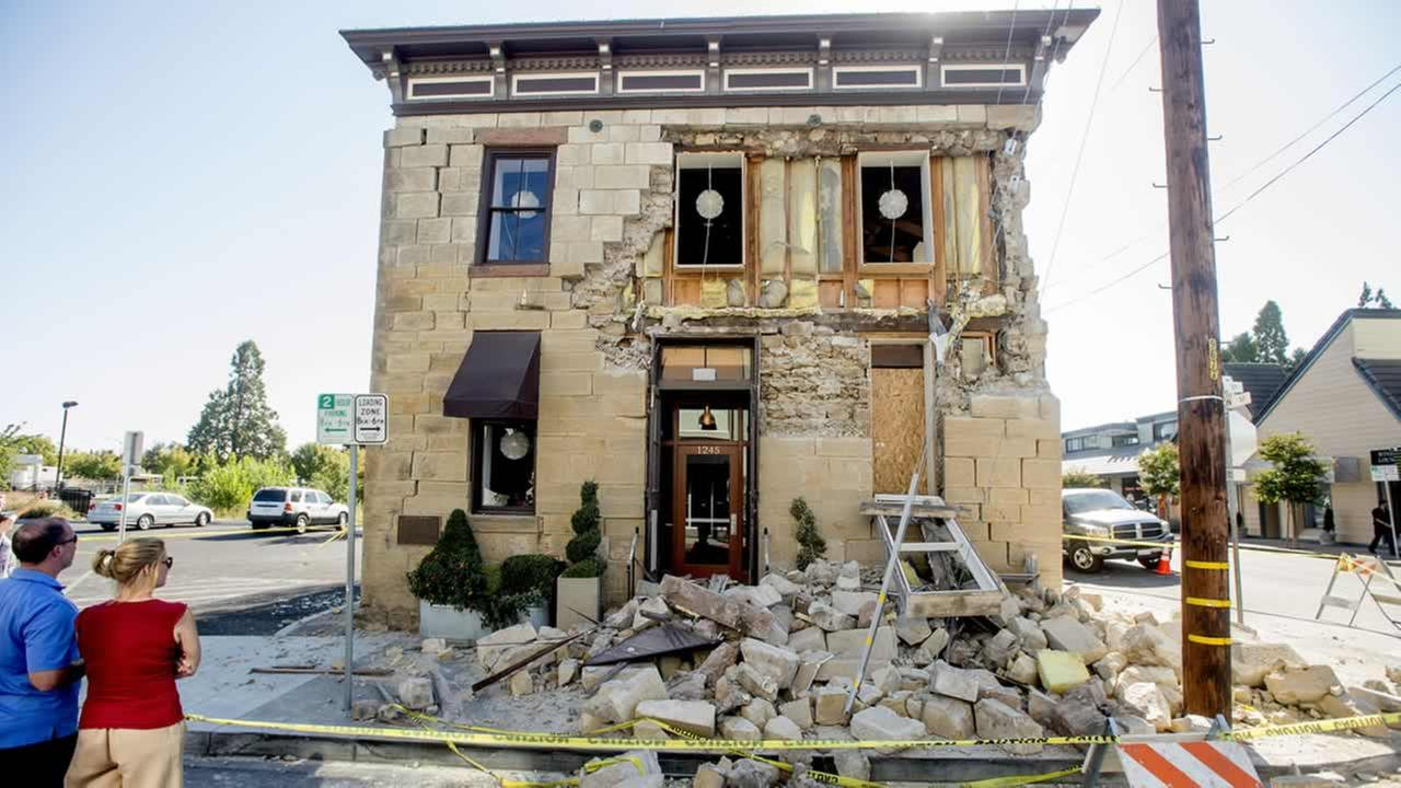 Pedestrians stop to examine a crumbling facade at the Vintners Collective tasting room in Napa, Calif., following an earthquake Sunday, Aug. 24, 2014.