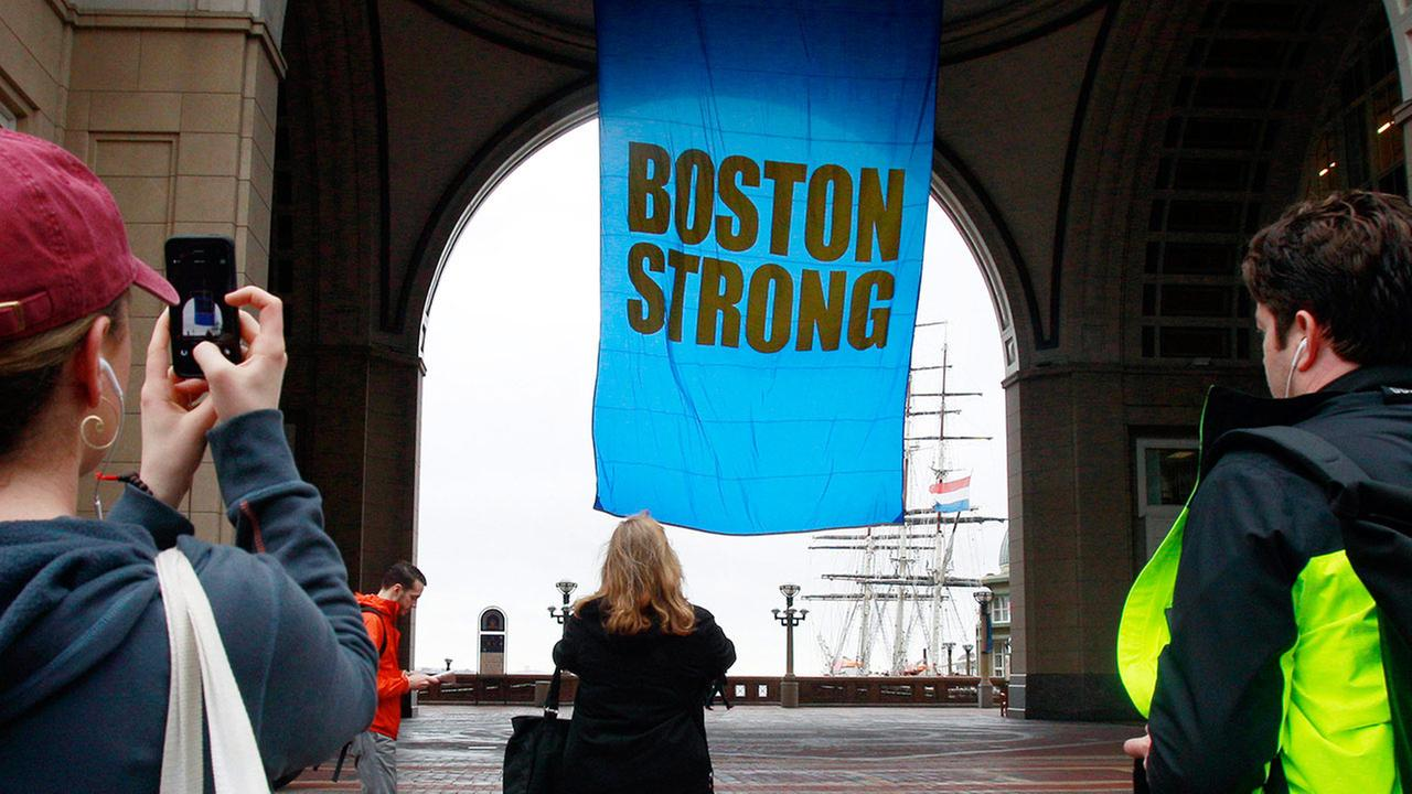 People photograph a banner reading Boston Strong as it hangs at Rowes Wharf on the first anniversary of the Boston Marathon bombings, Tuesday, April 15, 2014, in Boston.