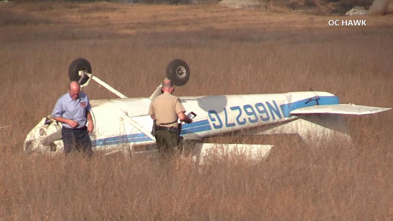Officials are investigating the crash of a small plane that landed upside down in a field in Corona.
