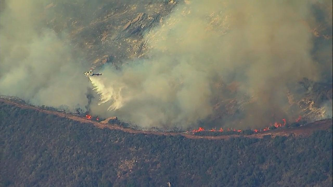 A helicopter drops water on active flames from the Thomas Fire in a file photo.