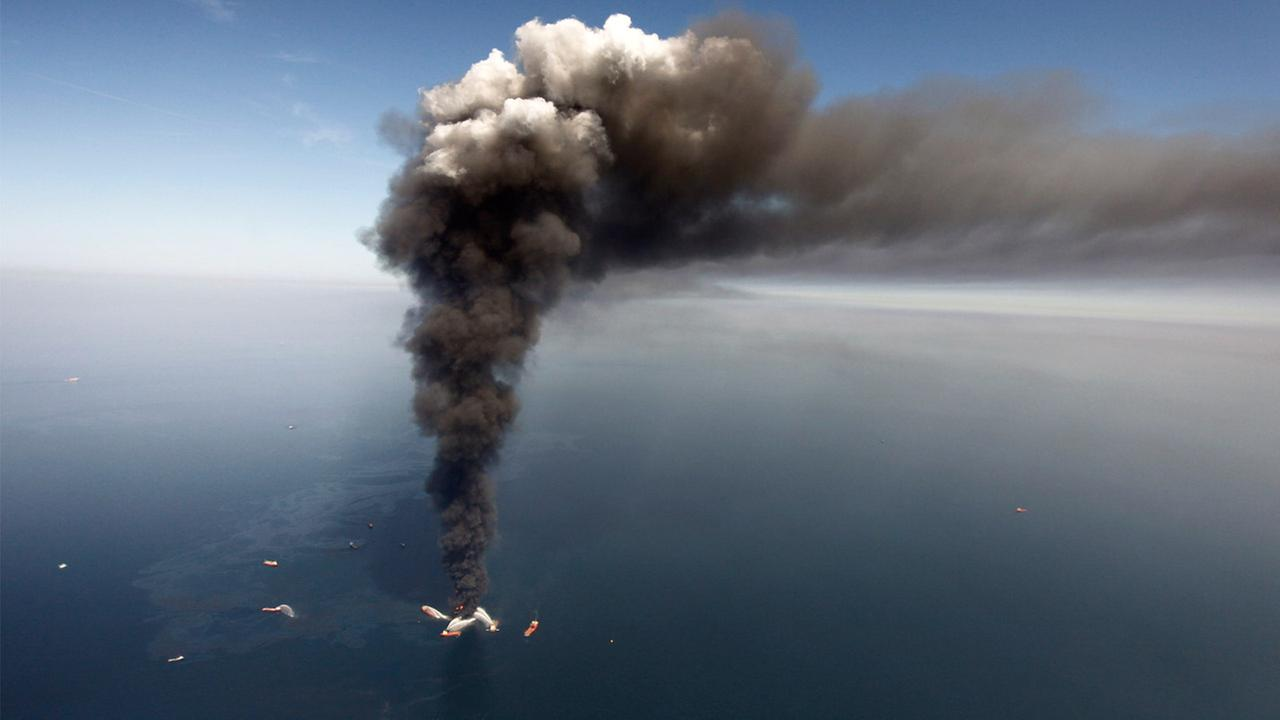 FILE - Wednesday, April 21, 2010: Oil can be seen in the Gulf of Mexico, more than 50 miles southeast of Louisianas tip, from fires on BPs Deepwater Horizon offshore oil rig.