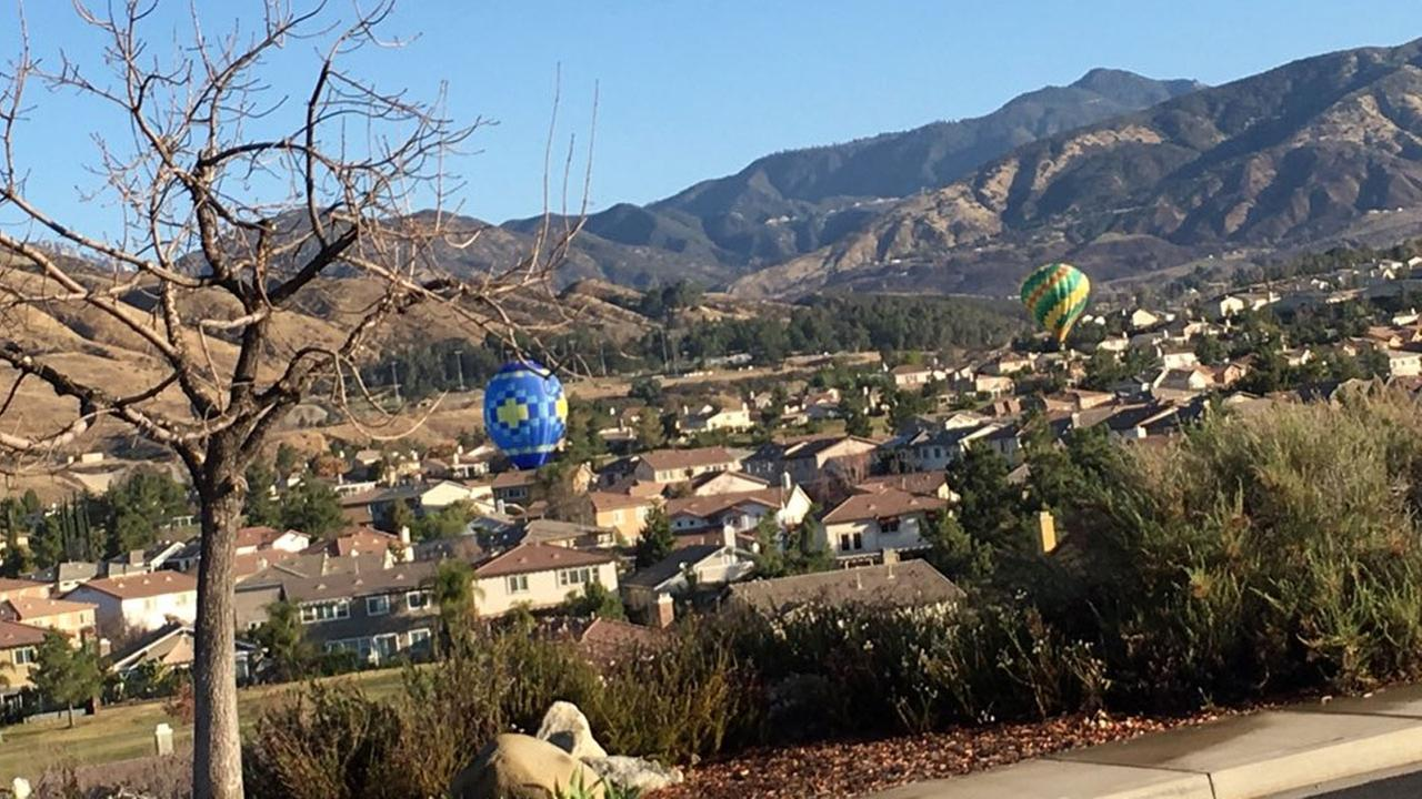 Two hot air balloons are shown flying over homes in the Chapman Heights neighborhood of Yucaipa around 8 a.m. on Tuesday, Feb. 6, 2018.