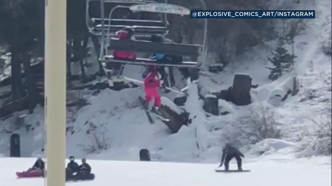 A 5-year-old girl is shown dangling from a chairlift while her ski instructor holds onto her hood until rescuers below can catch her on a tarp.