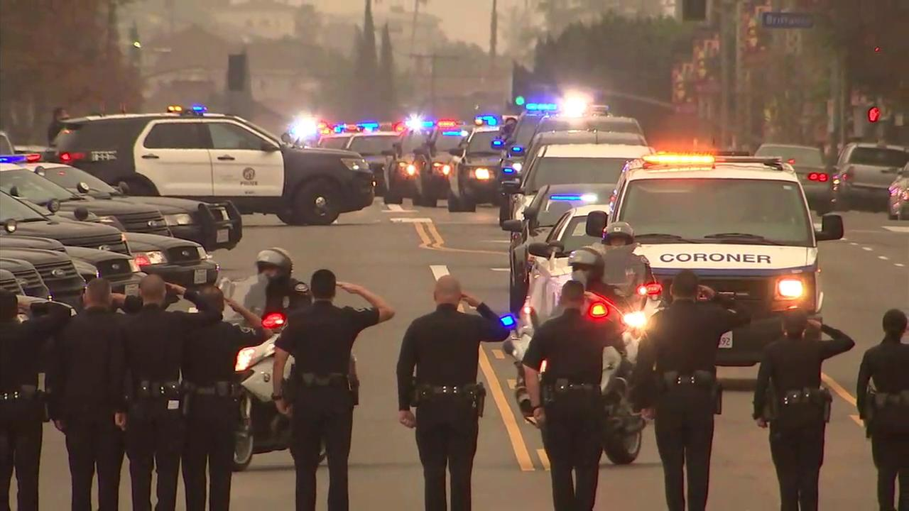 Fellow officers salute a procession escorts a slain Pomona police officer to the Los Angeles County coroners office on Saturday, March 3, 2018.