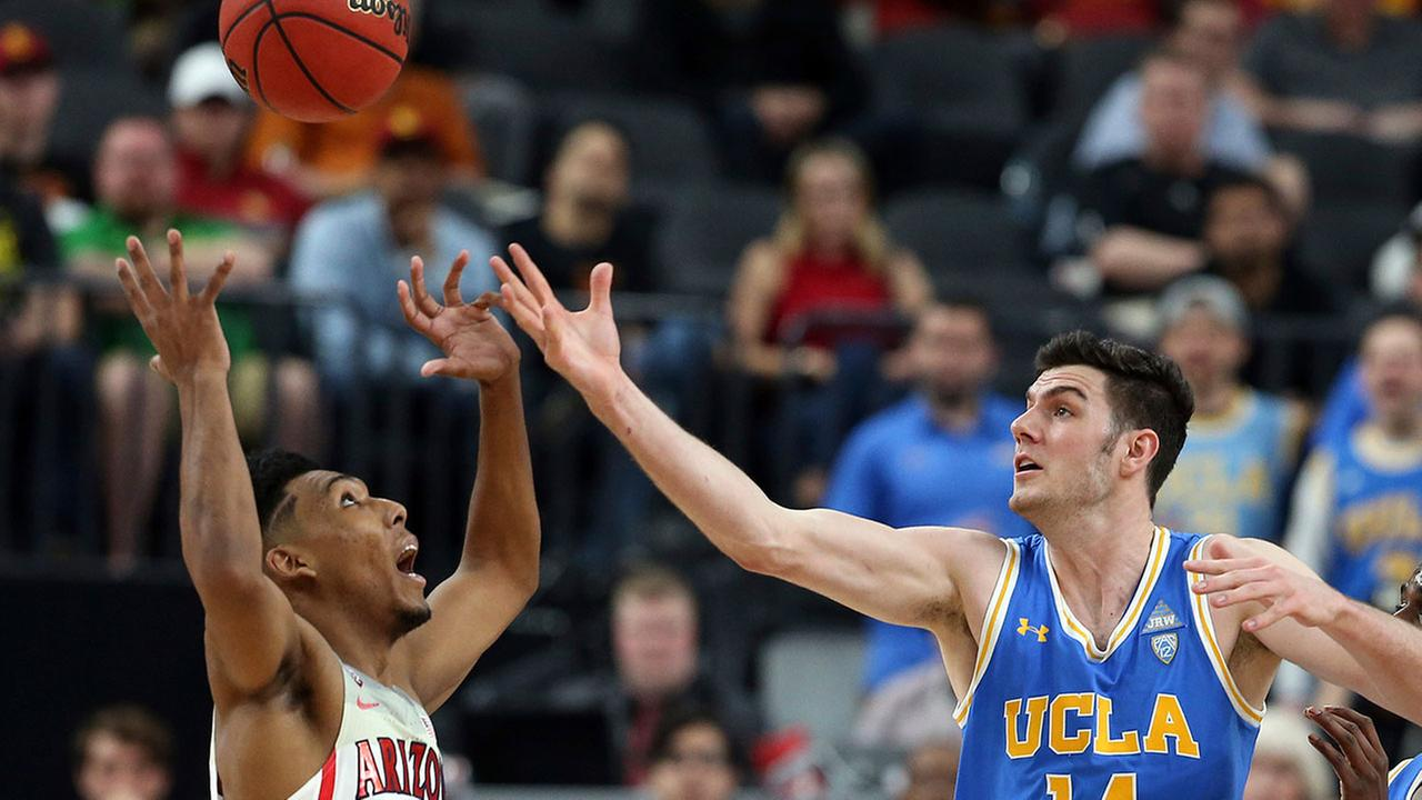 UCLAs Gyorgy Goloman and Arizonas Allonzo Trier reach for a loose ball during the semifinals of the Pac-12 mens tournament Friday, March 9, 2018, in Las Vegas.