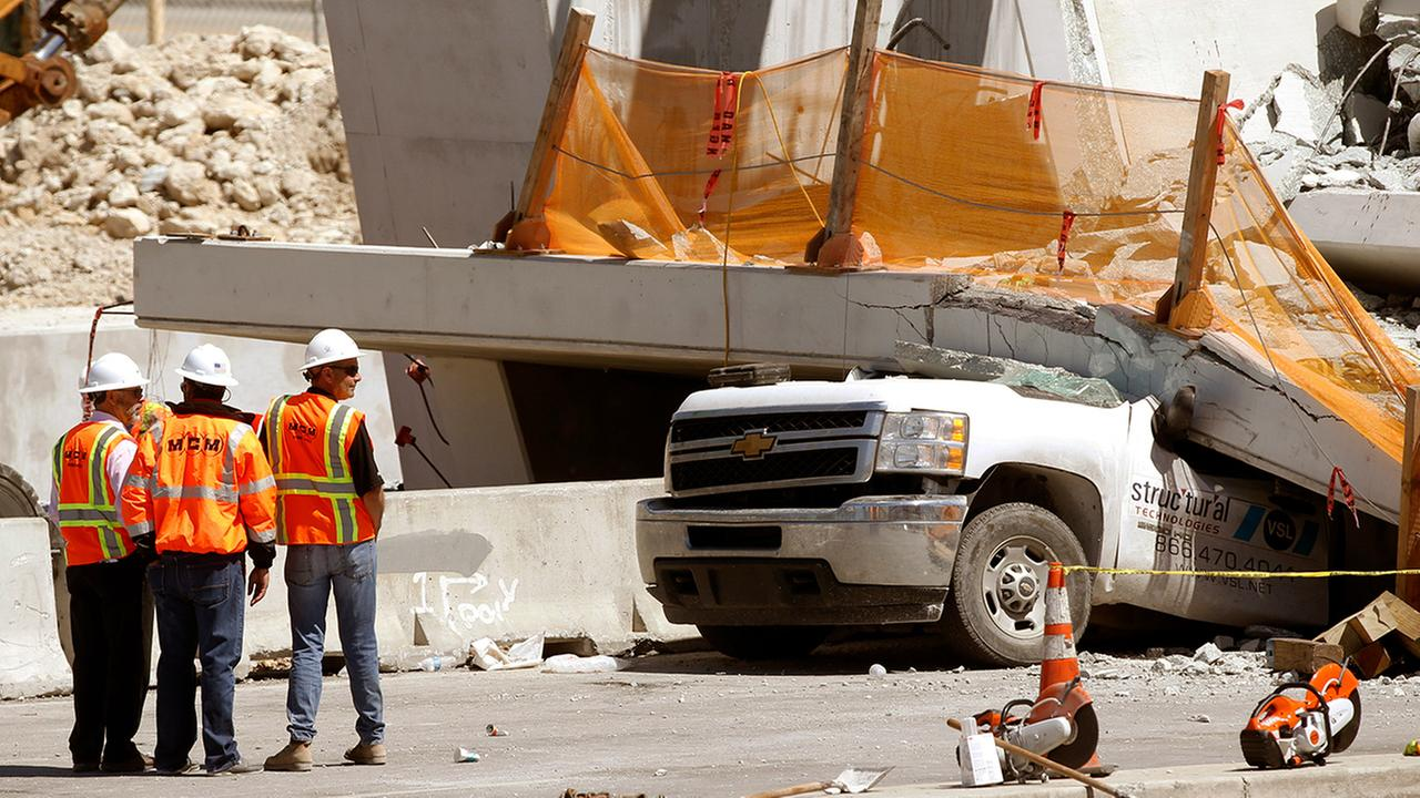 Workers stand next to a section of a collapsed pedestrian bridge, Friday, March 16, 2018, near Florida International University in the Miami area.