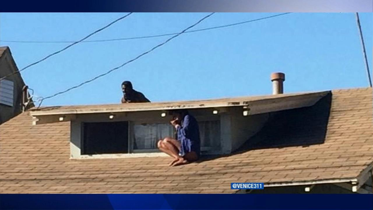A frightened resident in Venice hides on her roof, as a suspect looms nearby on Wednesday, Sept. 25, 2014.