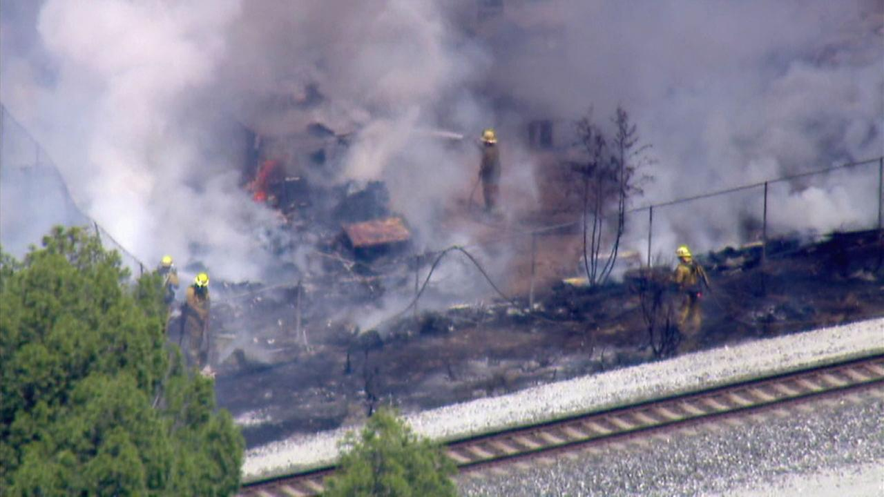 Firefighters are battling a brush fire that erupted near train tracks amid strong winds in the Acton area on Thursday, April 12, 2018.