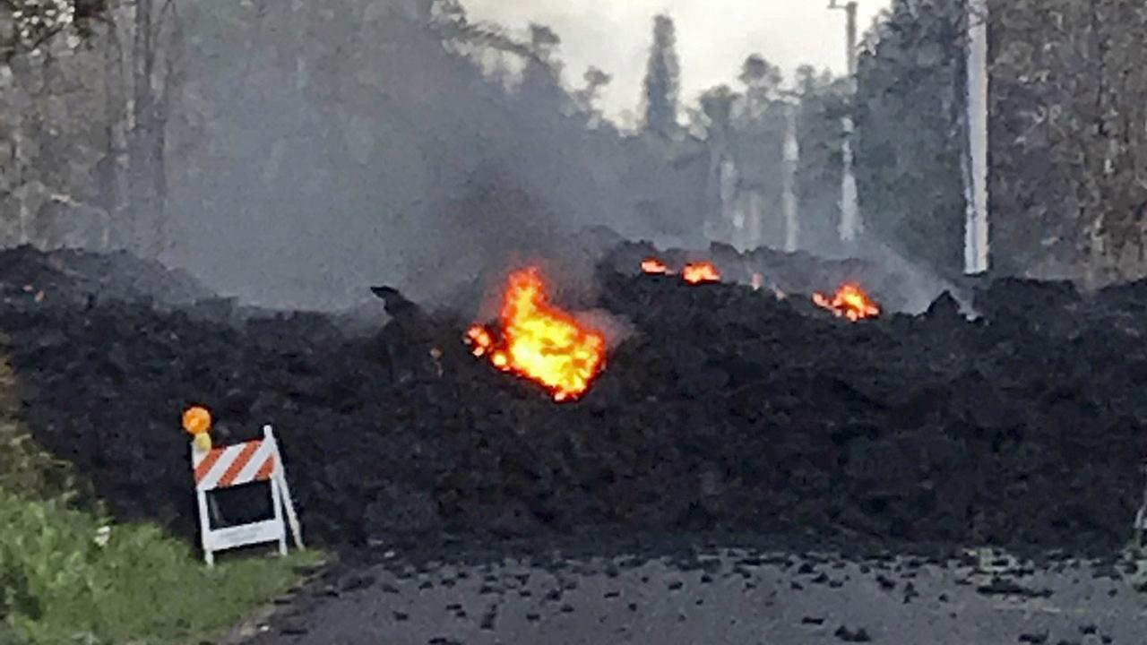 This photo provided by Hawaii Electric Light shows lava flowing over Mohala Street in the Leilani Estates area near Pahoa on the Big Island of Hawaii Friday, May 4, 2018.