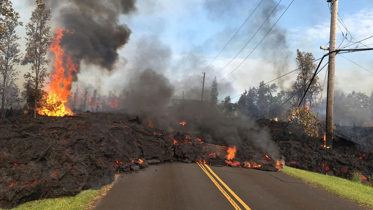 In this Saturday, May 5, 2018, photo provided by USGS, lava from Fissure 7 slowly advances to the northeast on Hookapu Street in the Leilani Estates subdivision in Pahoa, Hawaii.